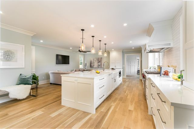 Large kitchen with white counter tops and wooden floors