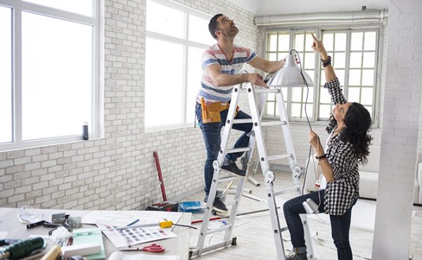 Young woman and a construction worker renovating an apartment