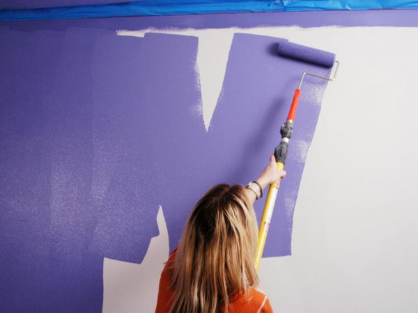 woman in an orange shirt painting the wall purple
