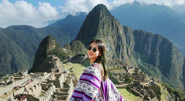 woman posing in front Machu Picchu