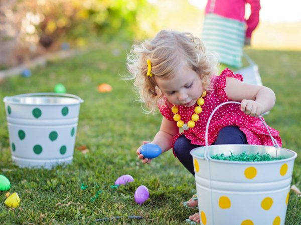 a baby in a cute red dress hunting for easter eggs in the garden