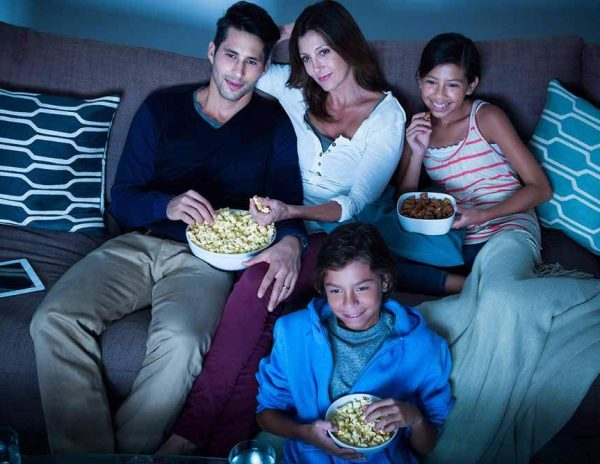 a family watching a movie and eating popcorn