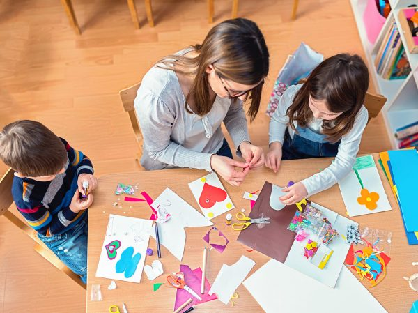 a mom with her kids on the livingroom floor doing arts and crafts